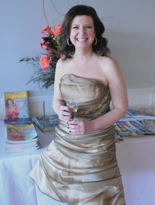 "CREDITS: Gold dress by Pesavento Couture at Elephant's Trunk in Mount Kisco (thank you Susan Ward, Robert and Rafael!); earrings by Jolie B. Ray at ROCKS in Armonk; at Aura Salon, kudos to Lu Camarena Meshulam for makeup and to hairdresser Dawn Hiller for the cascading curls–and to Ana for nails. Special thanks to ICD Contemporary Jewelry for a gorgeous bracelet and to March Boutique for a stunning black and gold cover up. Whispering Pines sent over a fabulous bouquet with the 10th anniversary issue of IC cleverly tucked inside the vase. Chappaqua's Joy's Balloons decorated the tables. Beascakes Bakery in Armonk created the ""CQ,"" multiple layer strawberry shortcake. Finally, The Flower Pot in Larchmont supplied the single stem roses for all. I so appreciate everyone's TLC on this special day. Photo by Amy Kerwin"