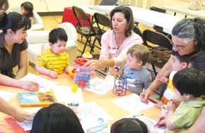 Volunteers work with children while their parents also participate in a Parenting Education class.