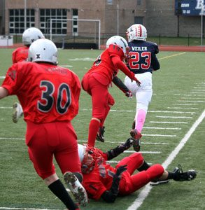 """#23 Matt Weiler in """"Beast Mode"""" running over the defenders on his way to one of many touchdowns in 2014. When Matt was not running for touchdowns, he was equally adept at throwing for touchdowns with the running back option pass play. Photo by Shari Fruhling"""