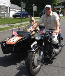 "This year's parade ""won't be the same"" without Gabby Rosenfeld, who was awarded a French Legion of Honor medal. Here, Gabby in the motorcade alongside his son Eric."