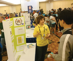 Zachary Eichenberger explains the team's app to interested convention goers. Leslie Shih Photo