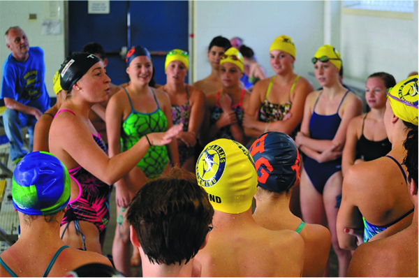 Ariana gives tips and advice to a rapt group of competitive young swim- mers at the Boys and Girls Club in Mount Kisco.