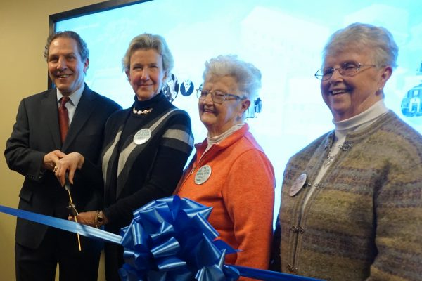 From left: Joel Seligman and Nancy Karch lead a ribbon cutting ceremony with Pat Reilly and Joan Stewart in front of the interactive historical timeline.