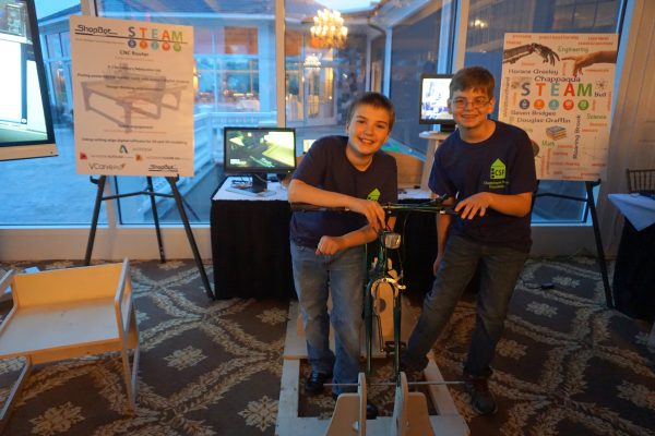 "Jason Lavender (right) and Nate Meyer, 6th graders at Seven Bridges Middle School, described the ""bicycle generator"" they designed. ""The bicycle has a generator that powers a television through a battery, capacitor and inverter that connect to the television."""