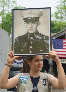 Meaghan Townsend holding a picture of Francis M. Murphy, Korean War Veteran, Silver Star Recipient. Meaghan, of Girl Scout Troop 1023, also read an oral history of Robert L. Sheddon, WWII Veteran.
