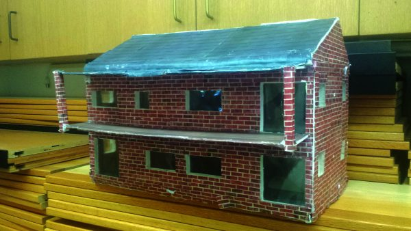 Model of a passive solar home with elements of sound, light, motion, and a sensor, designed and built by an Intro to Engineering student at Greeley.