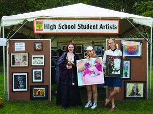Byram Hills High School seniors (l to r) Juliana Zepf, a ceramicist and paper sculptor, Gabrielle Kleinberg, painter, and Allegra Samsen, photographer, hold up some of their art on display at the Armonk Outdoor Art Show outside a tent dedicated to the work of 24 student artists primarily from Armonk but also from surrounding towns, whose work was juried into the show, on September 24, 2016. Photo © 2016 Marianne A. Campolongo